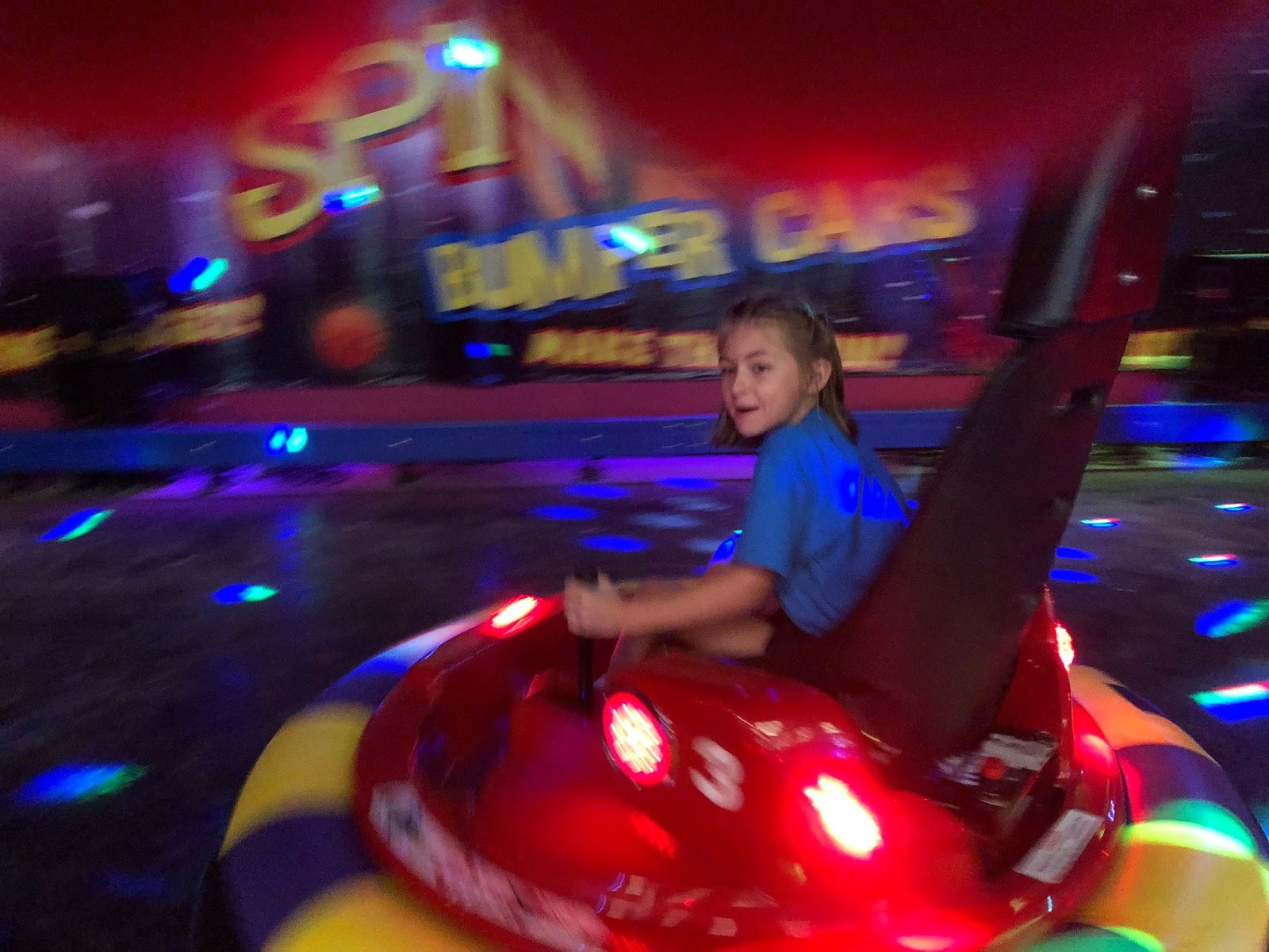 A girl is riding on a bumper car at The Lightning Bug
