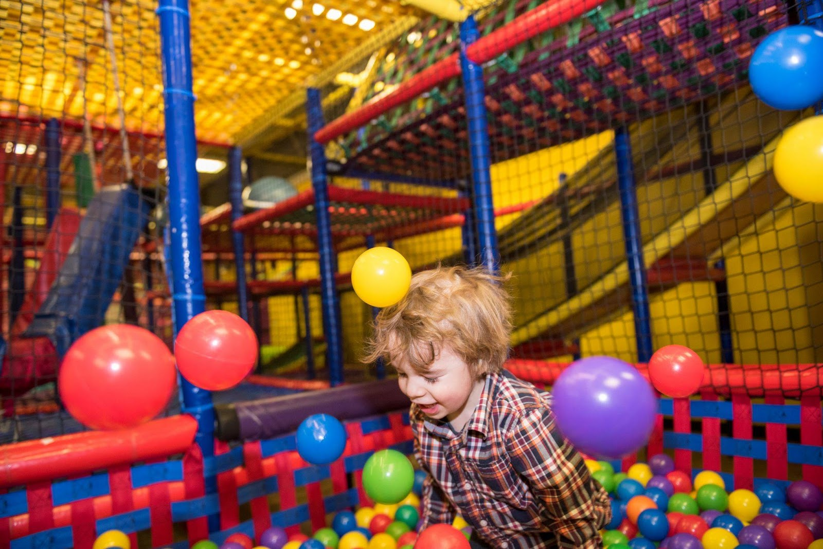 A boy is happily playing in a ball pit at Giggles and Smiles