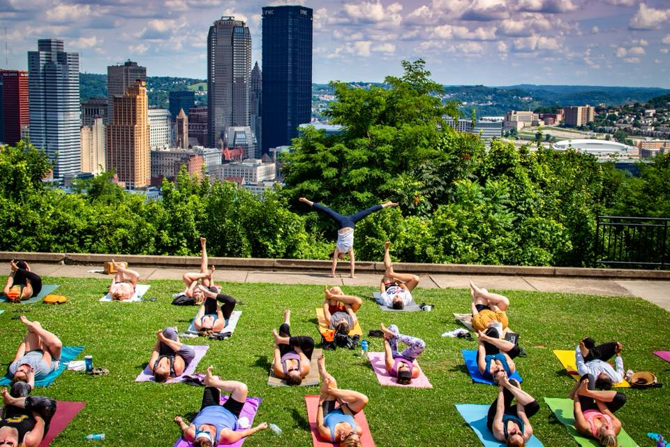 BTS Yoga Collective doing yoga overlooking city skyline