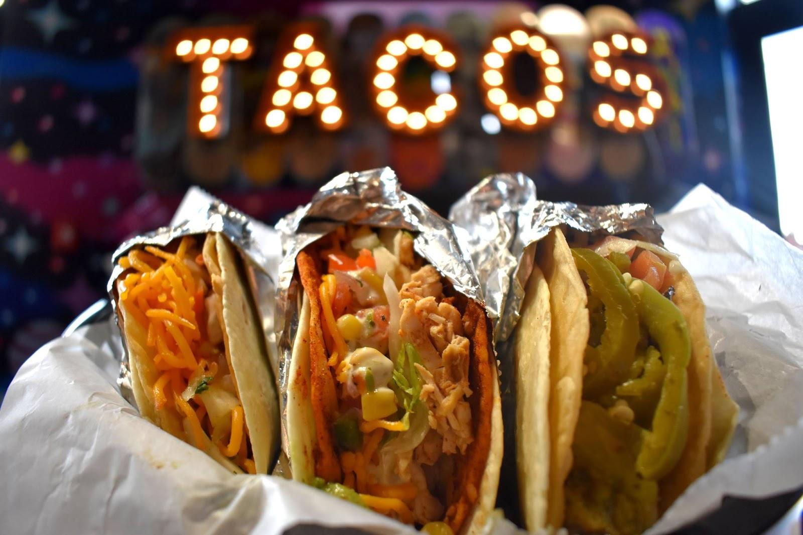 "Three tacos under ""Taco"" Sign"