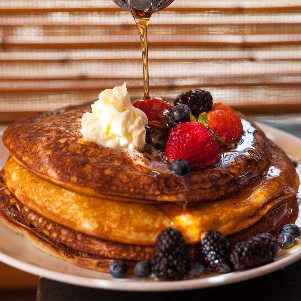 Warm syrup dripping over pancakes
