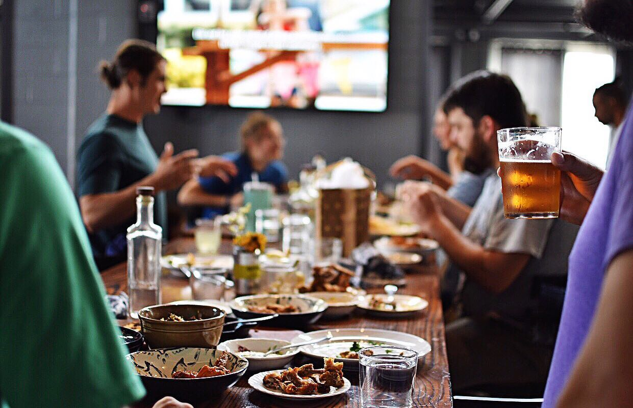 a long wood table filled with people and food
