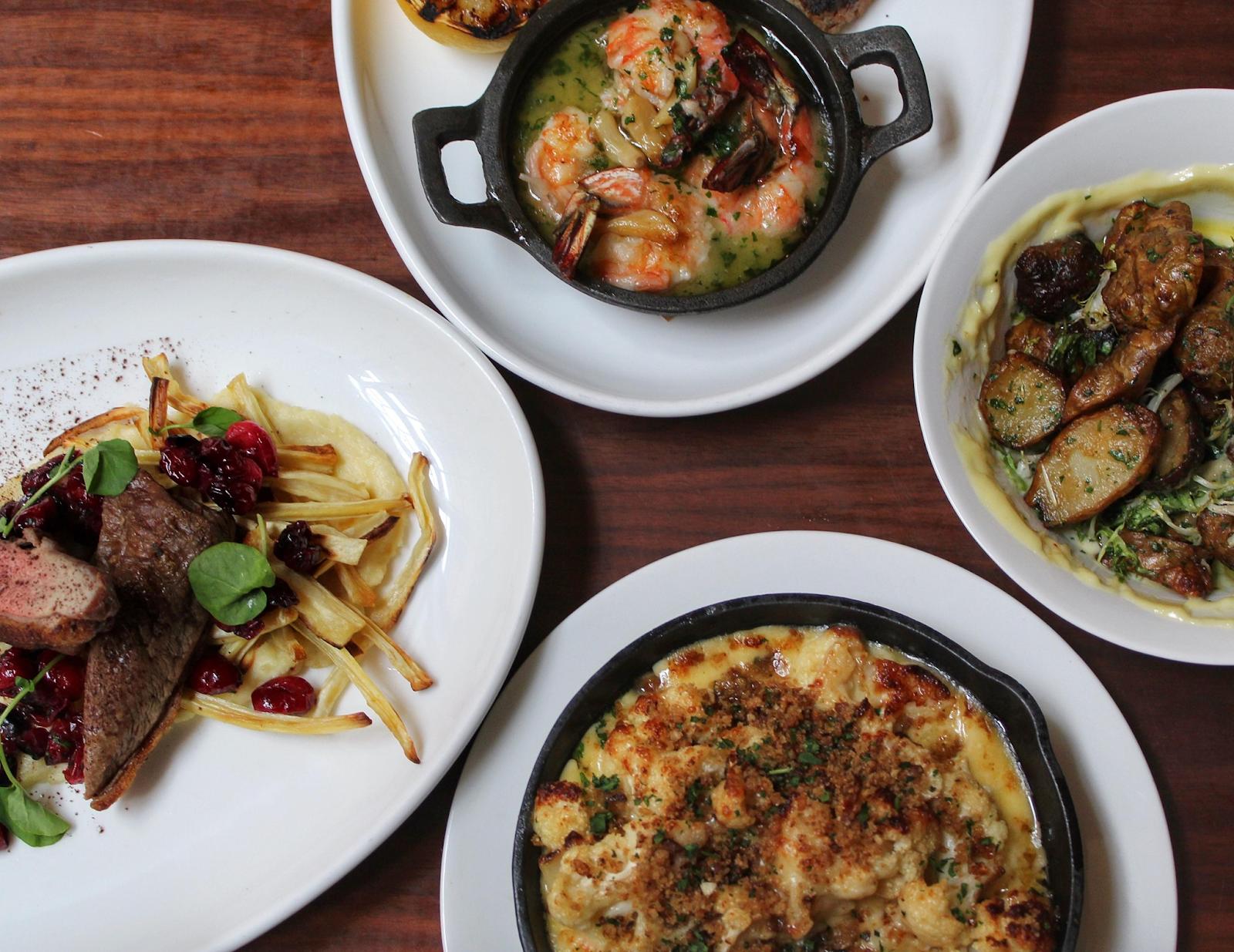 Three plates of dinner one shrimp, one steak, one has potatoes