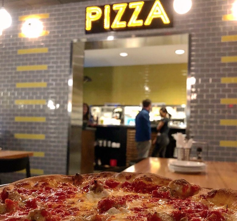 Pizza sign with a pepperoni pizza in foreground