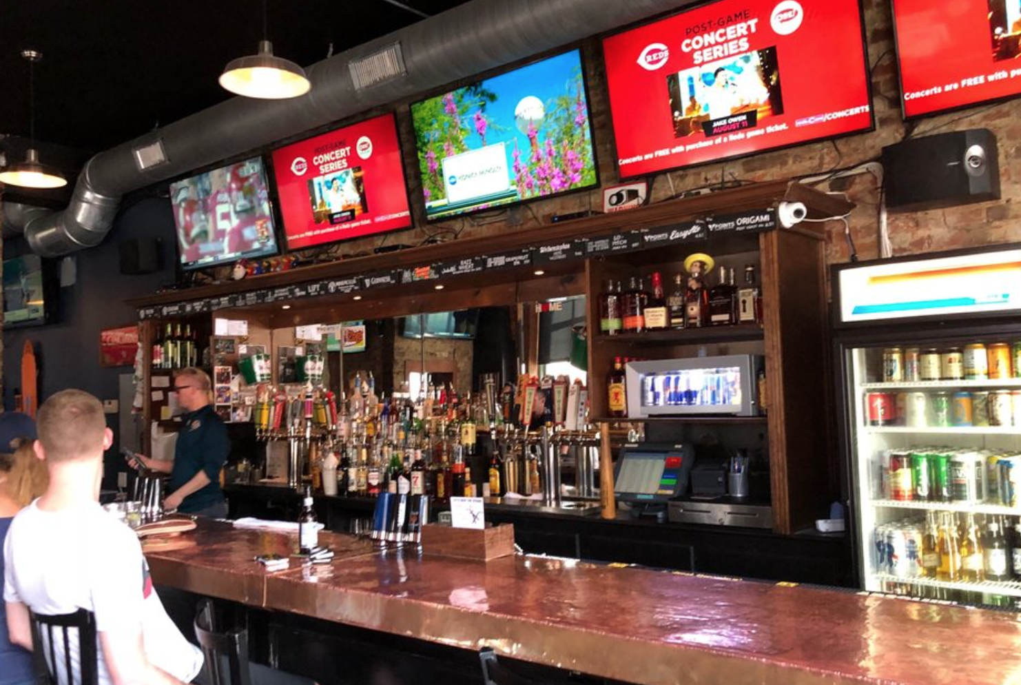 Sports bar with screens and a fridge full of beer