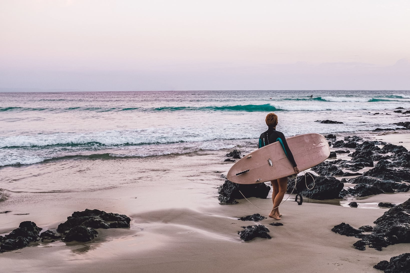 A surfer getting ready for an early morning surf in Australia