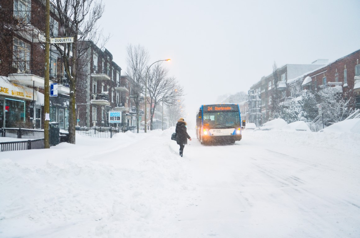 A snowy street in Montreal with the bus and a woman