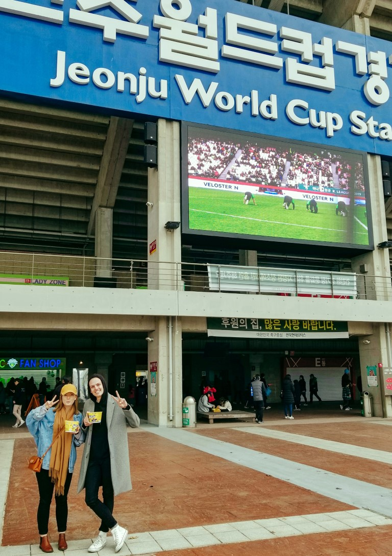 A couple standing in front of the Jeonju World Cup Stadium