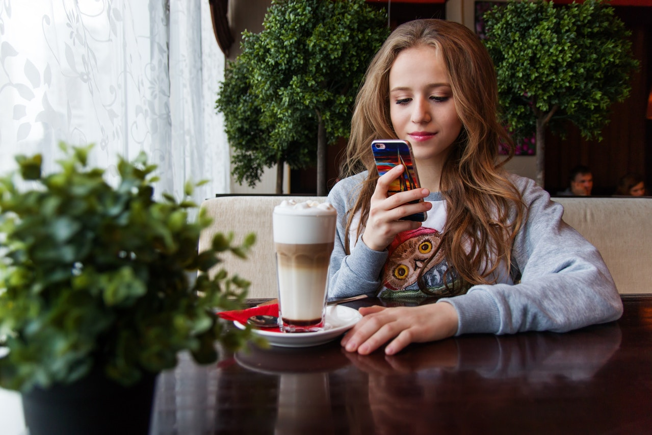 girl looking at her phone at a coffee shop