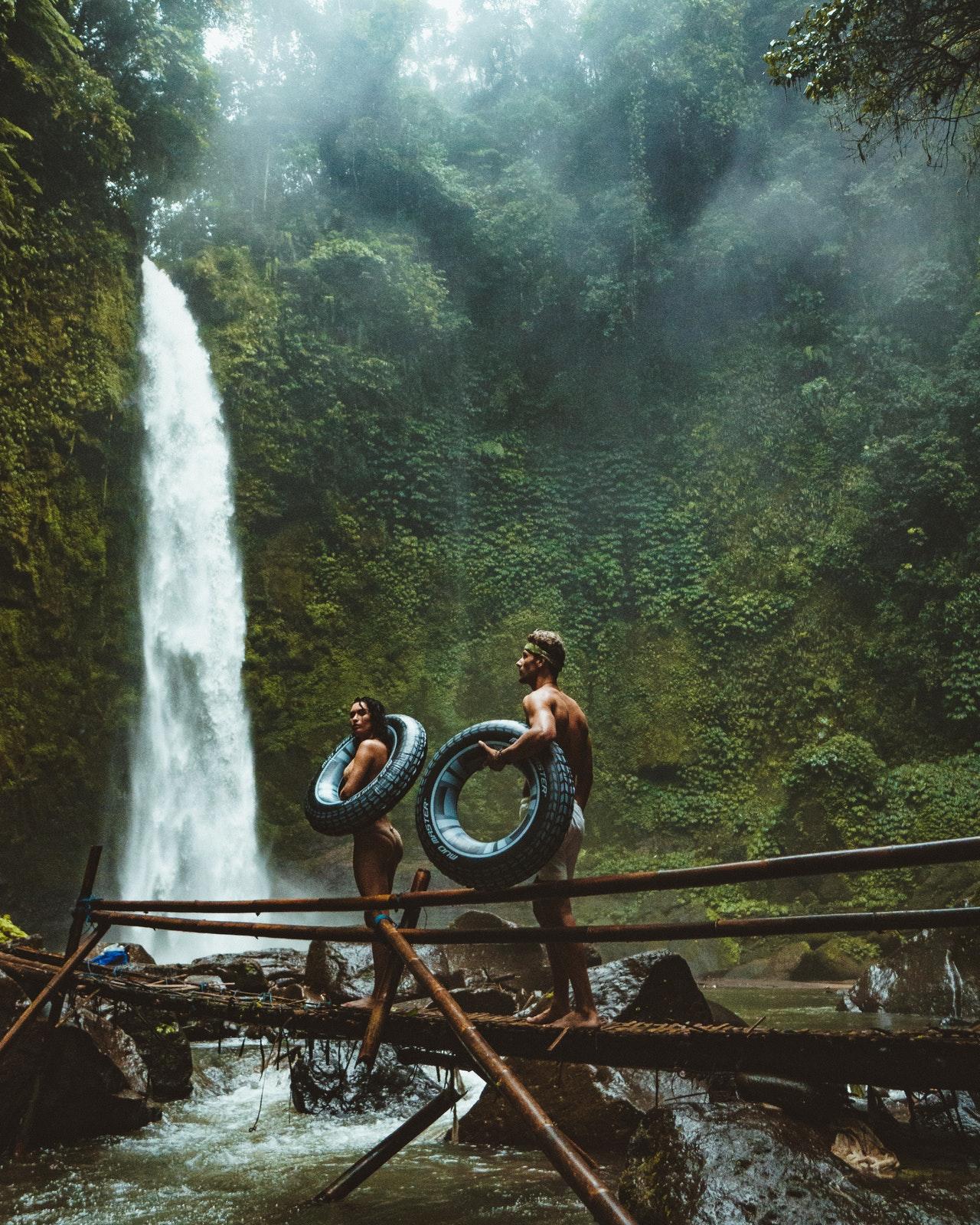 couple exploring waterfall in lush green jungle