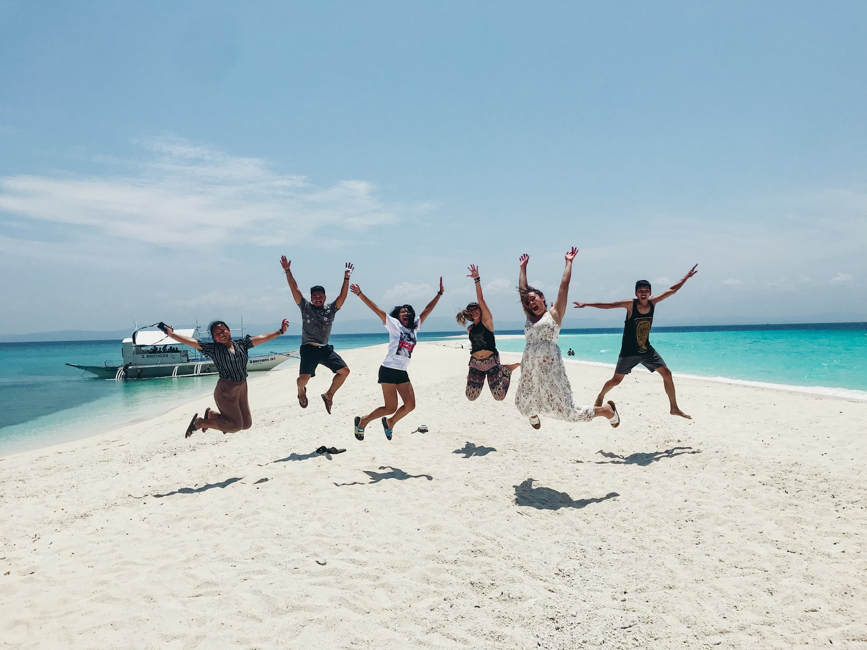 Friends jumping on a small strip of beach in the Philippines