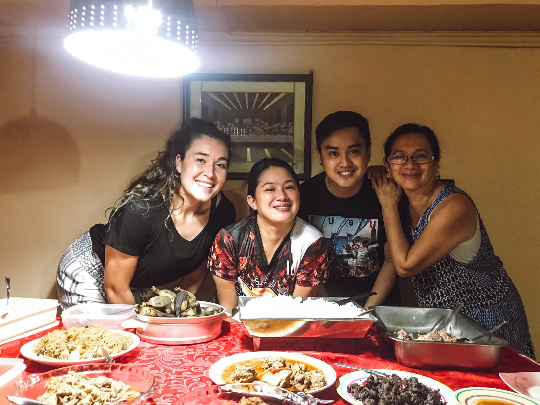 A welcoming family and a friend eating a big meal together in the Philippines