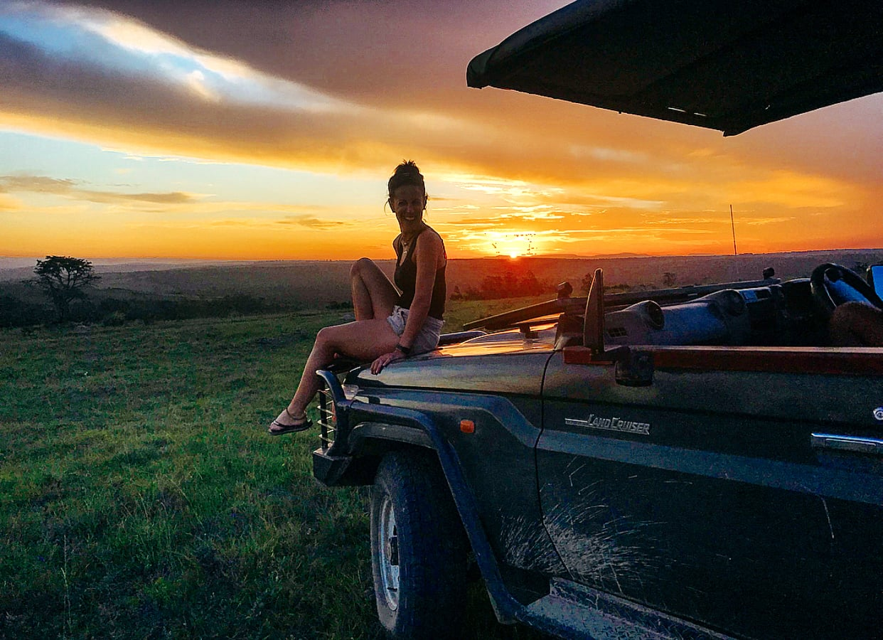 Woman sitting on the front of a jeep, watching the sunset in South Africa