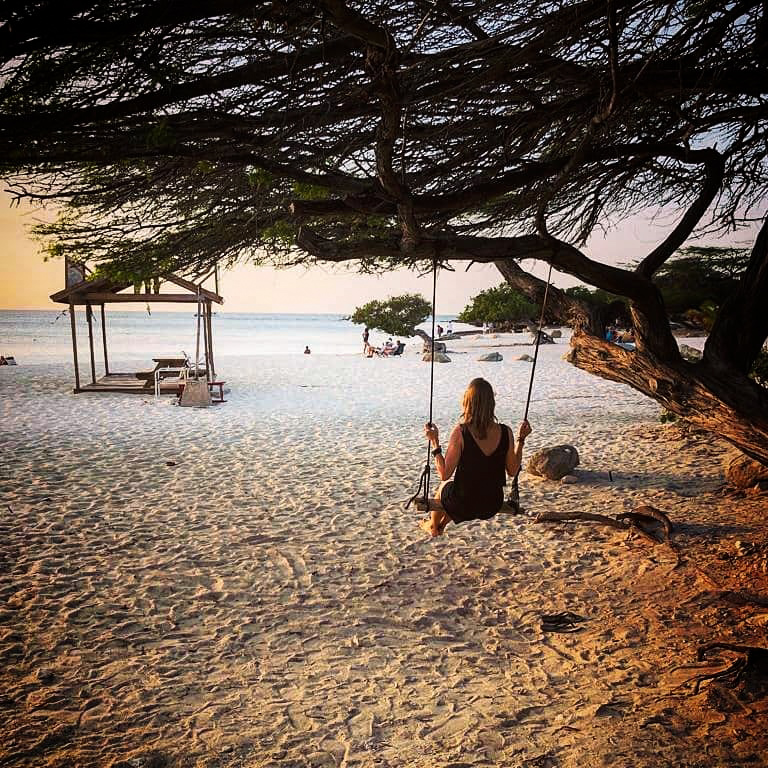 Woman on a swing on the beach watching the sunset in Aruba