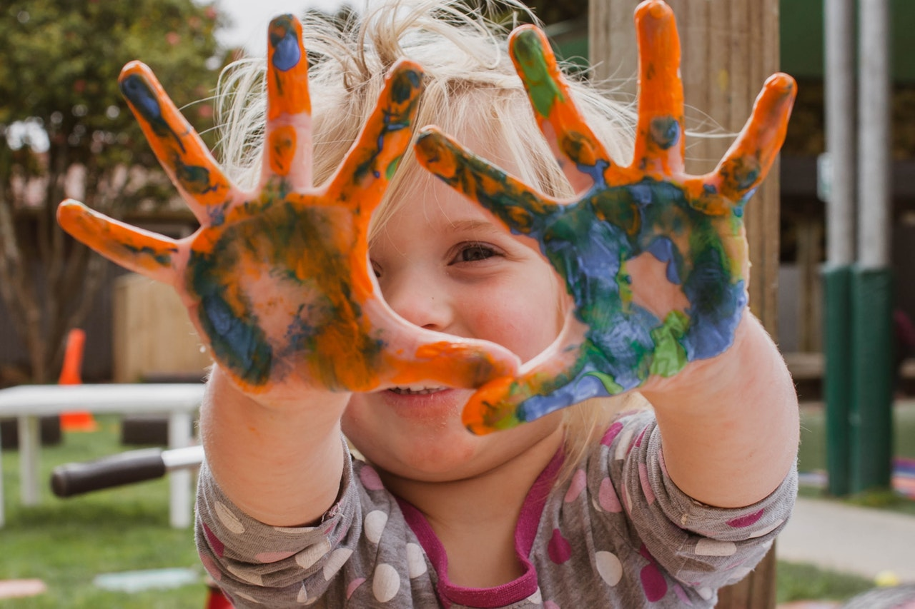 happy child getting messy with finger paint