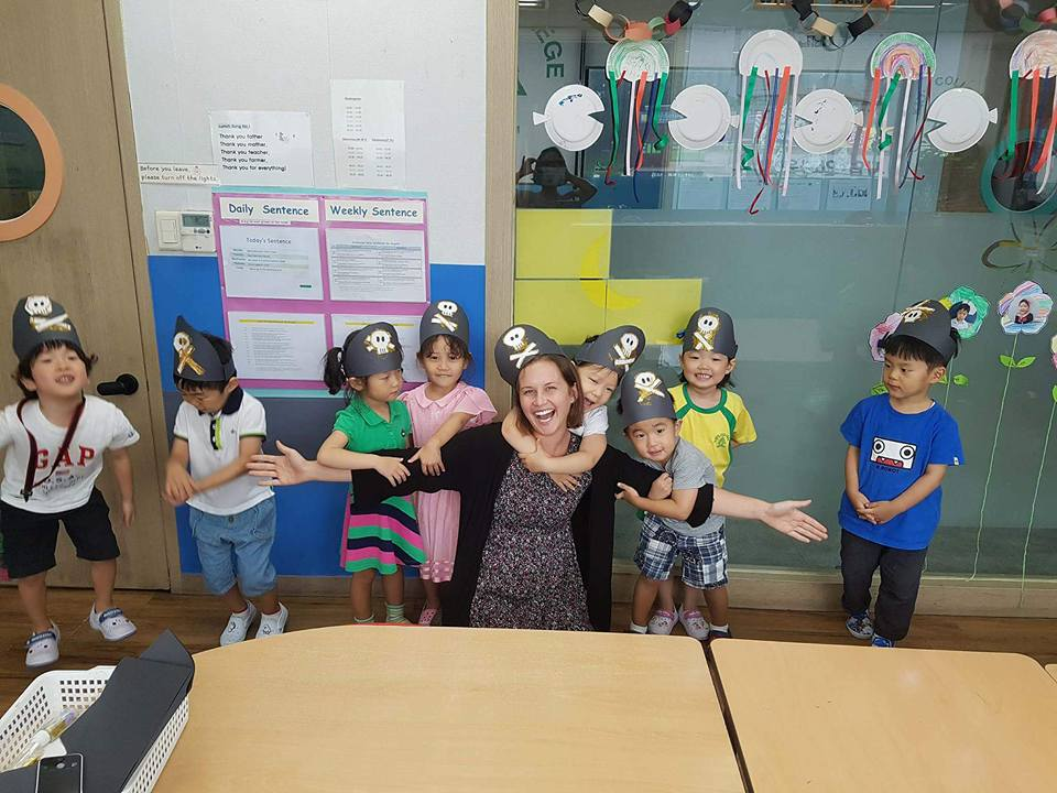 teacher getting hugs from students while in pirate hats in guri, korea