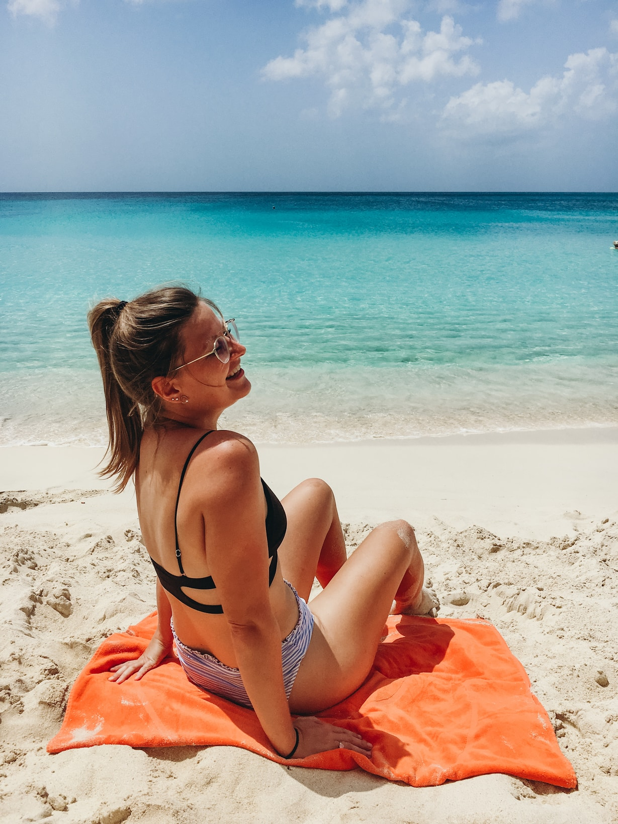 A woman sitting on a towel in the sand laughing with her friends at the beach in Sint Maarten