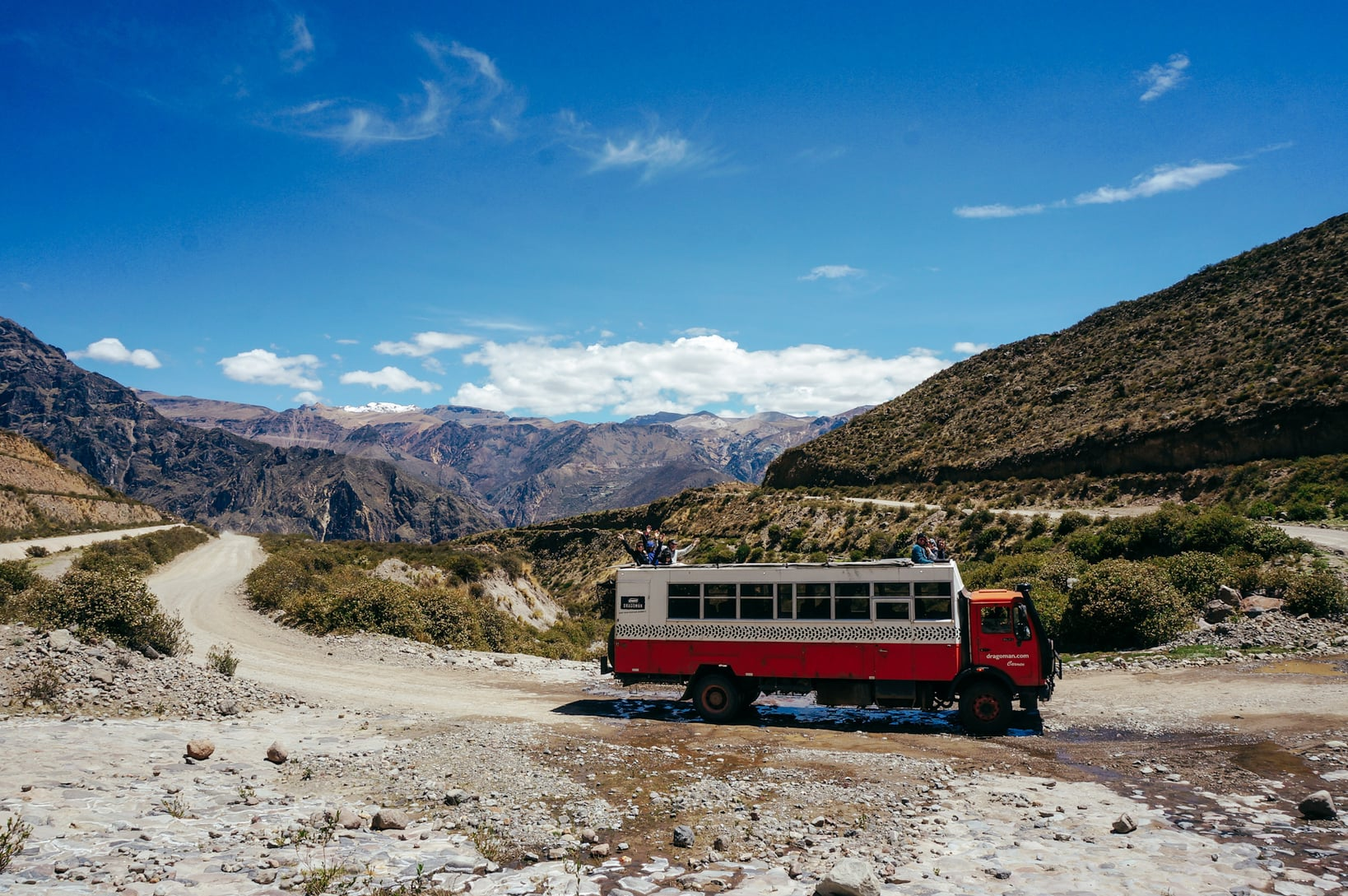 Overland red and white Dragoman Tour bus parked at Colca Canyon, Peru.