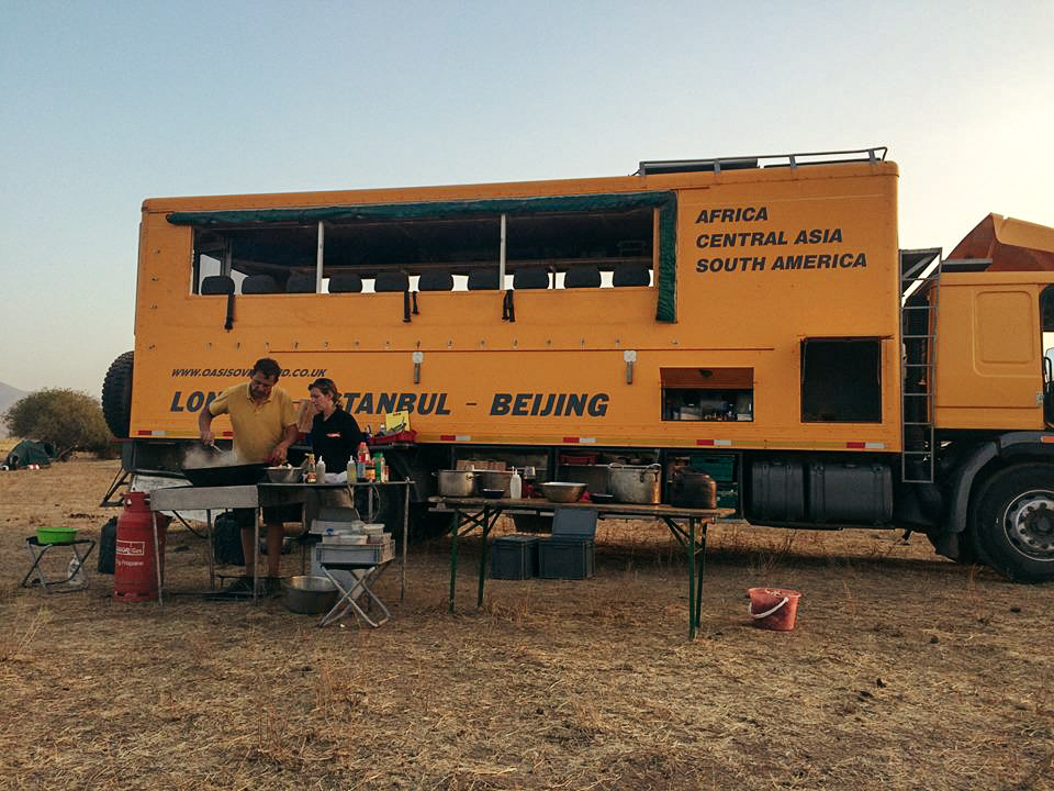 Yellow overland tour bus making dinner in Kazakhstan with Oasis Overland