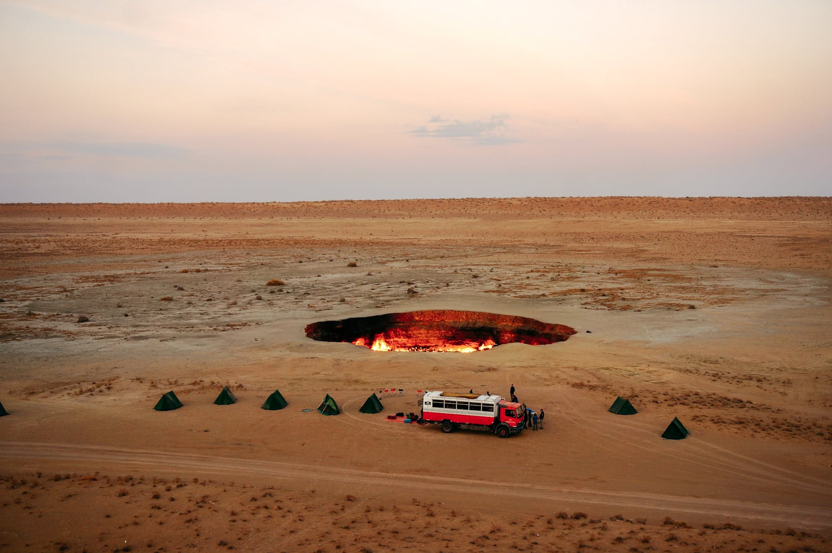 Dragoman Tour bus parked beside Darvasa gas crater in Turkmenistan