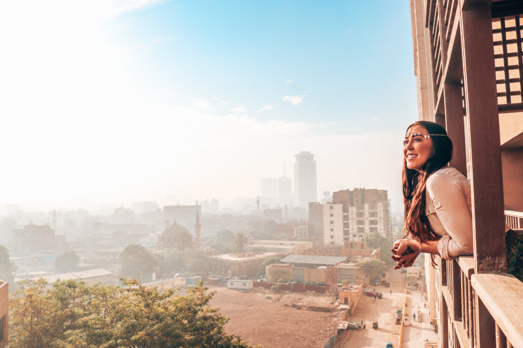 A solo female traveler on a solo trip to Egypt looking out over Cairo