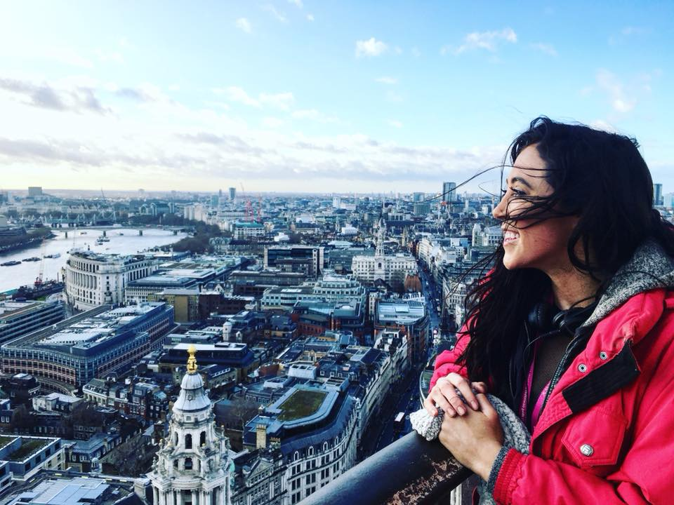 Solo female traveler enjoying her first solo trip to London from lookout point over the city