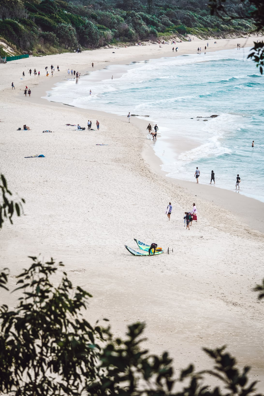 view of a white sand beach in Australia dotted with sunbathers and people walking in the suf