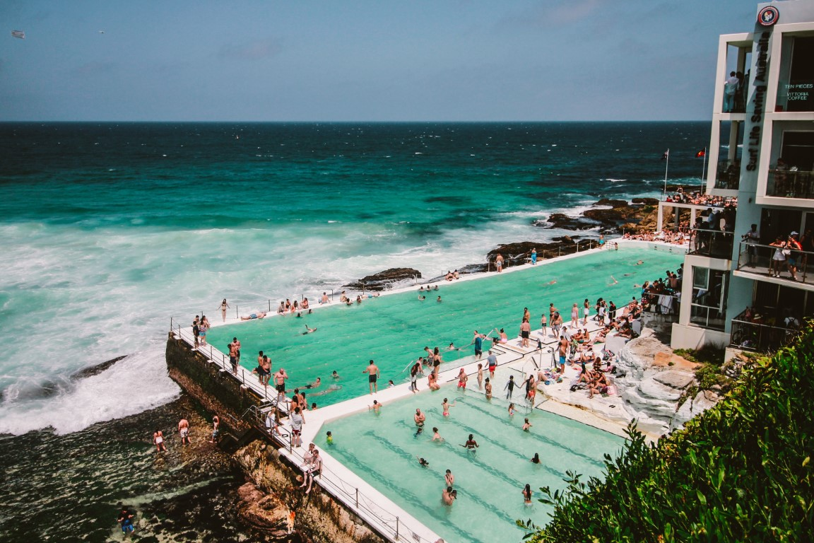 A crowded swimming pool perched at the ocean  on Bondi Bond