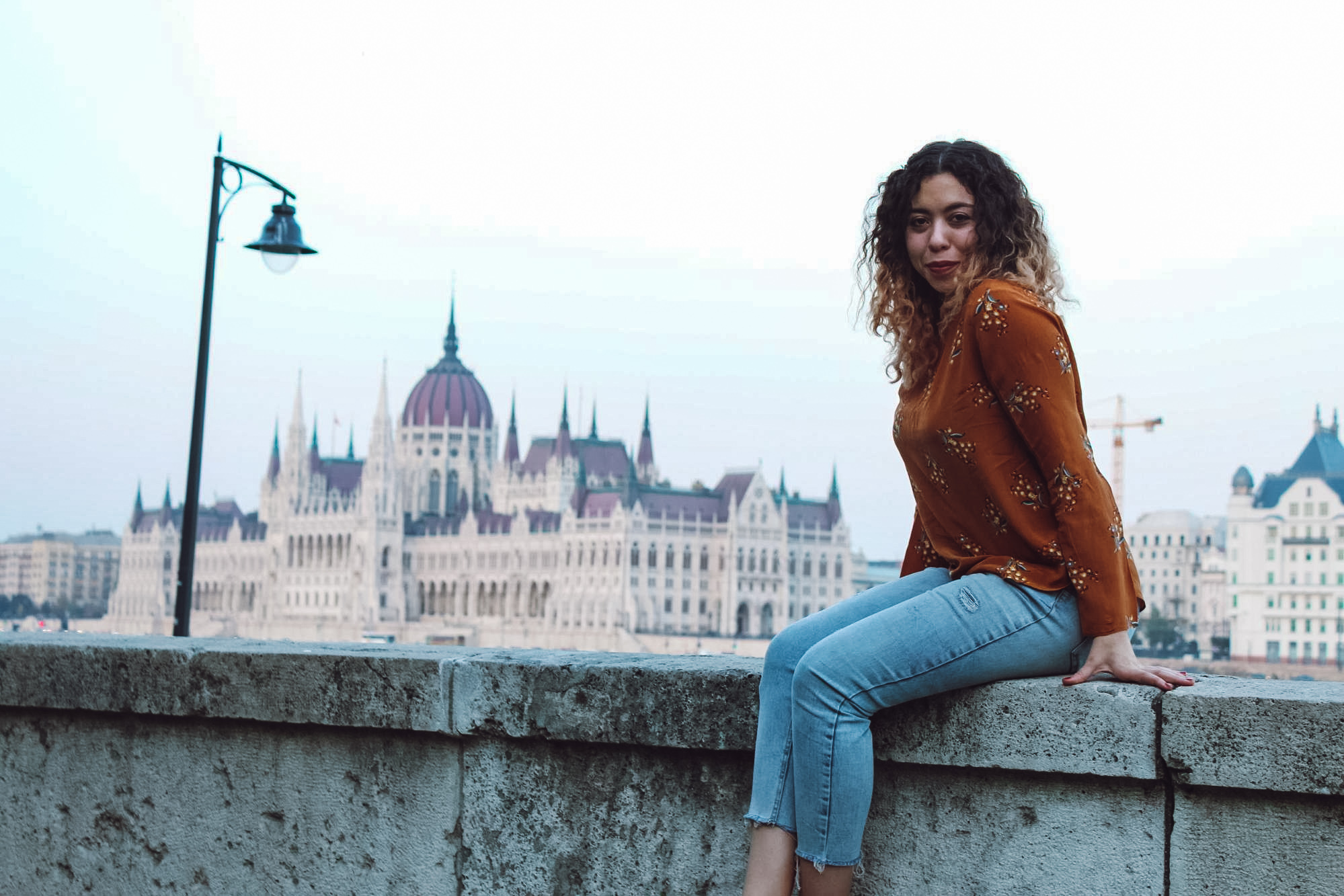 Woman sitting on ledge in Budapest with Parliment building in the background