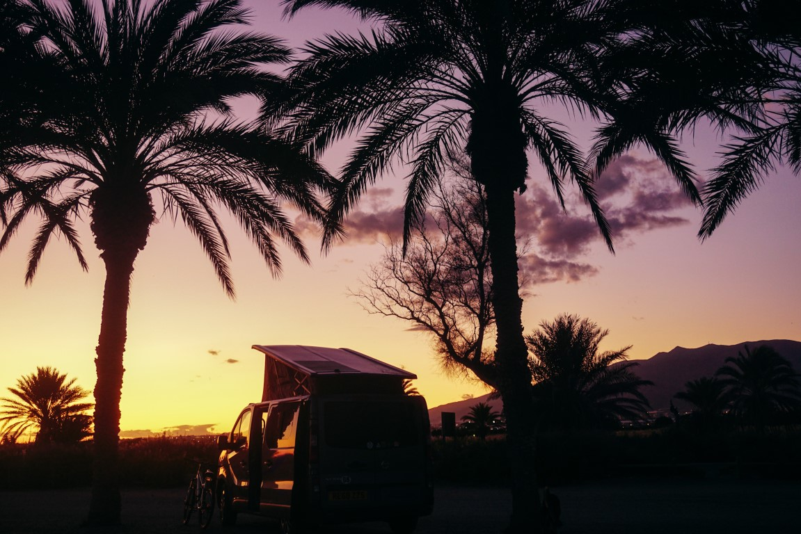 camper van at purple and yellow sunset parked between palm trees
