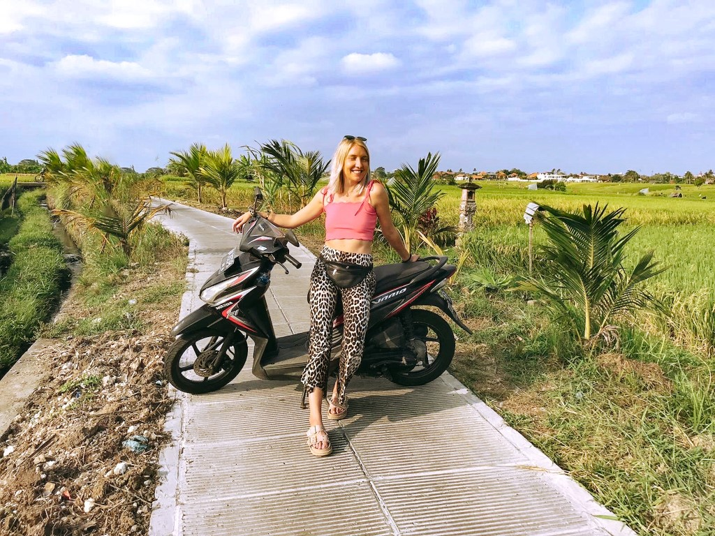 An expat woman posing with her motorbike in Bali