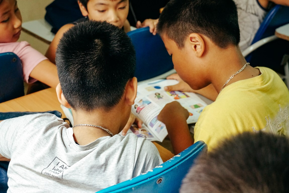 A group of students sharing a book in Vietnam