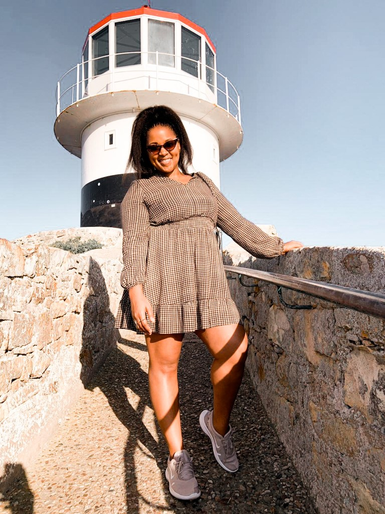 The lighthouse at Cape Point, South Africa with girl posing in front of it