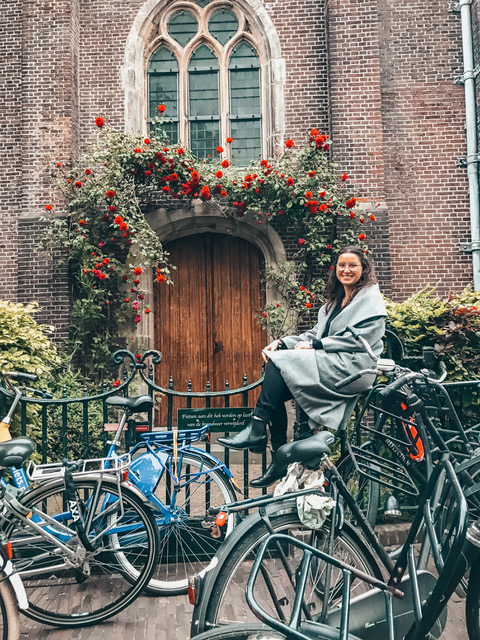 A woman in Amsterdam sitting on a bike