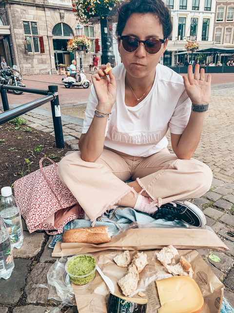 A woman having a picnic on the cobblestone eating gouda cheese in Gouda