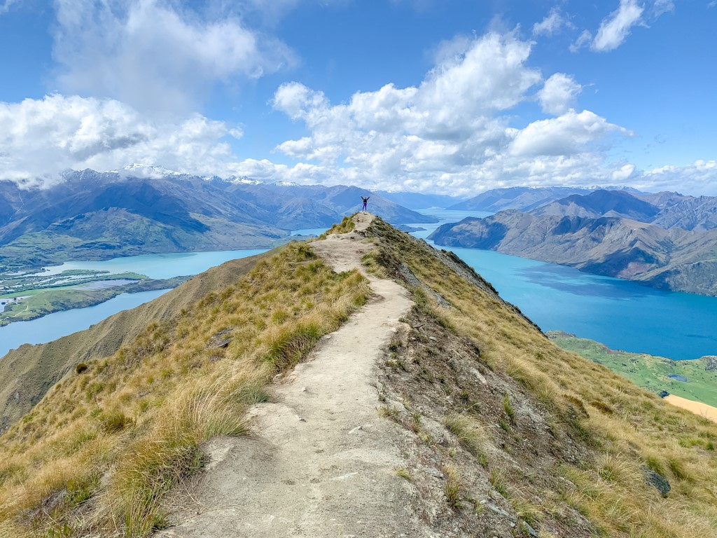 Solo female standing at summit on a beautiful clear day overlooking more mountains and a lake in New Zealand
