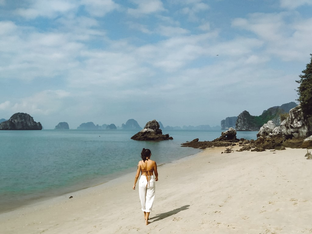 A digital nomad taking advantage of being location independent strolling the beach in Ha Long Bay, Vietnam