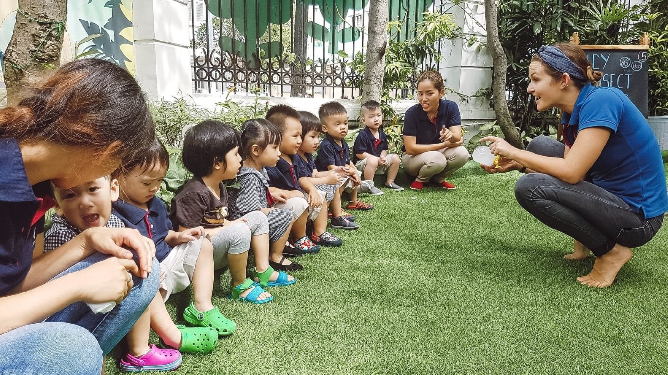 An English teacher holding a block of ice to play a sensory game with toddler students in Vietnam