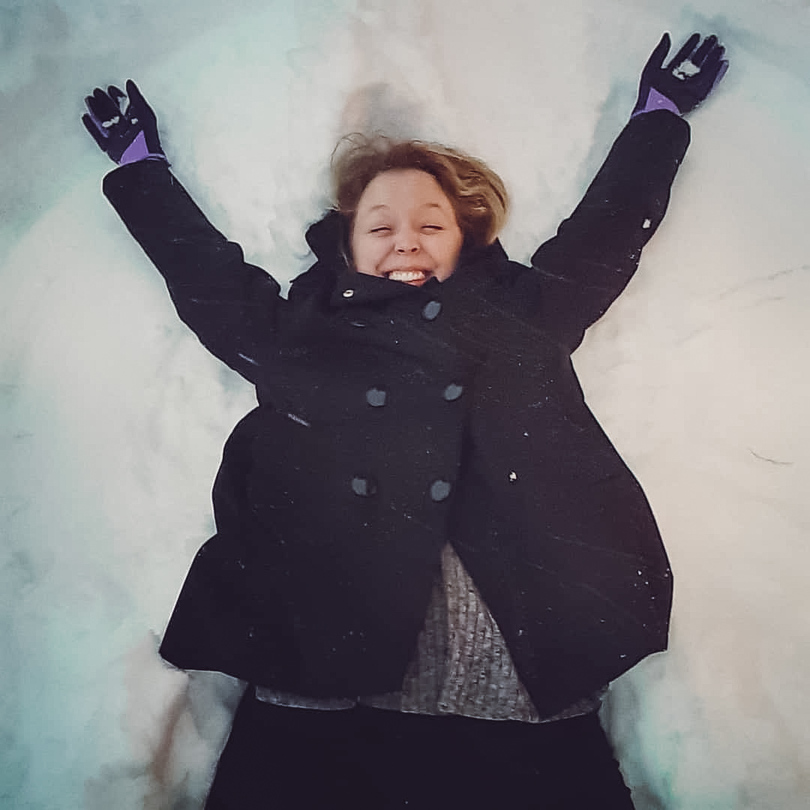 Happy female expat enjoying her first winter ever by making a snow angel in Germany