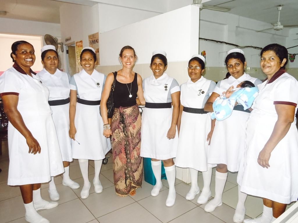 An international travel nurse smiling with a group of local nurses while on a tour of the hospital