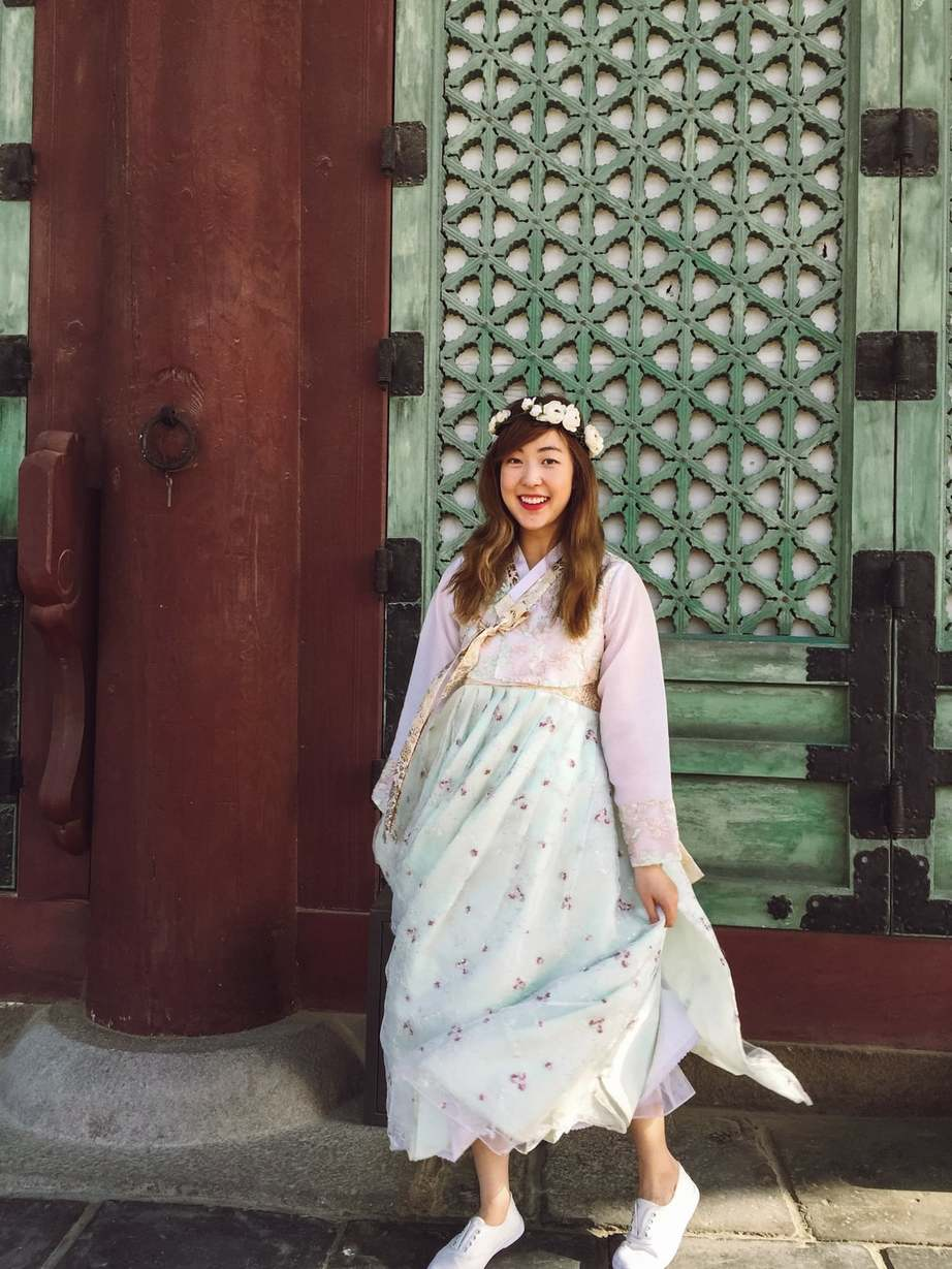 A foreigner living in Seoul having fun wearing the tranditional hanbok dress at a temple