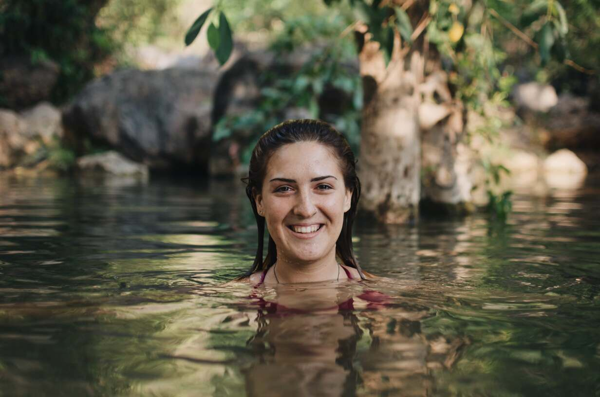 An expat woman who lives abroad in Myanmar swimming in a river