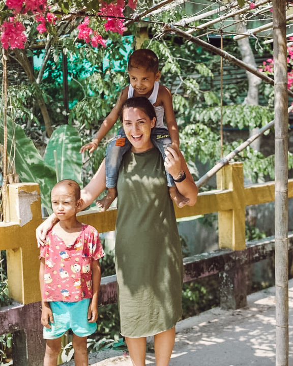An expat teacher outside with 2 students in Myanmar