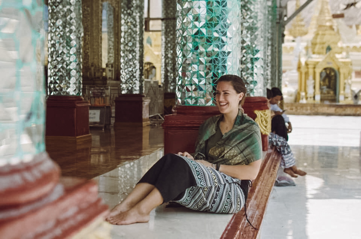 A foreign expat from Slovenia in a temple barefoot and smiling at a temple