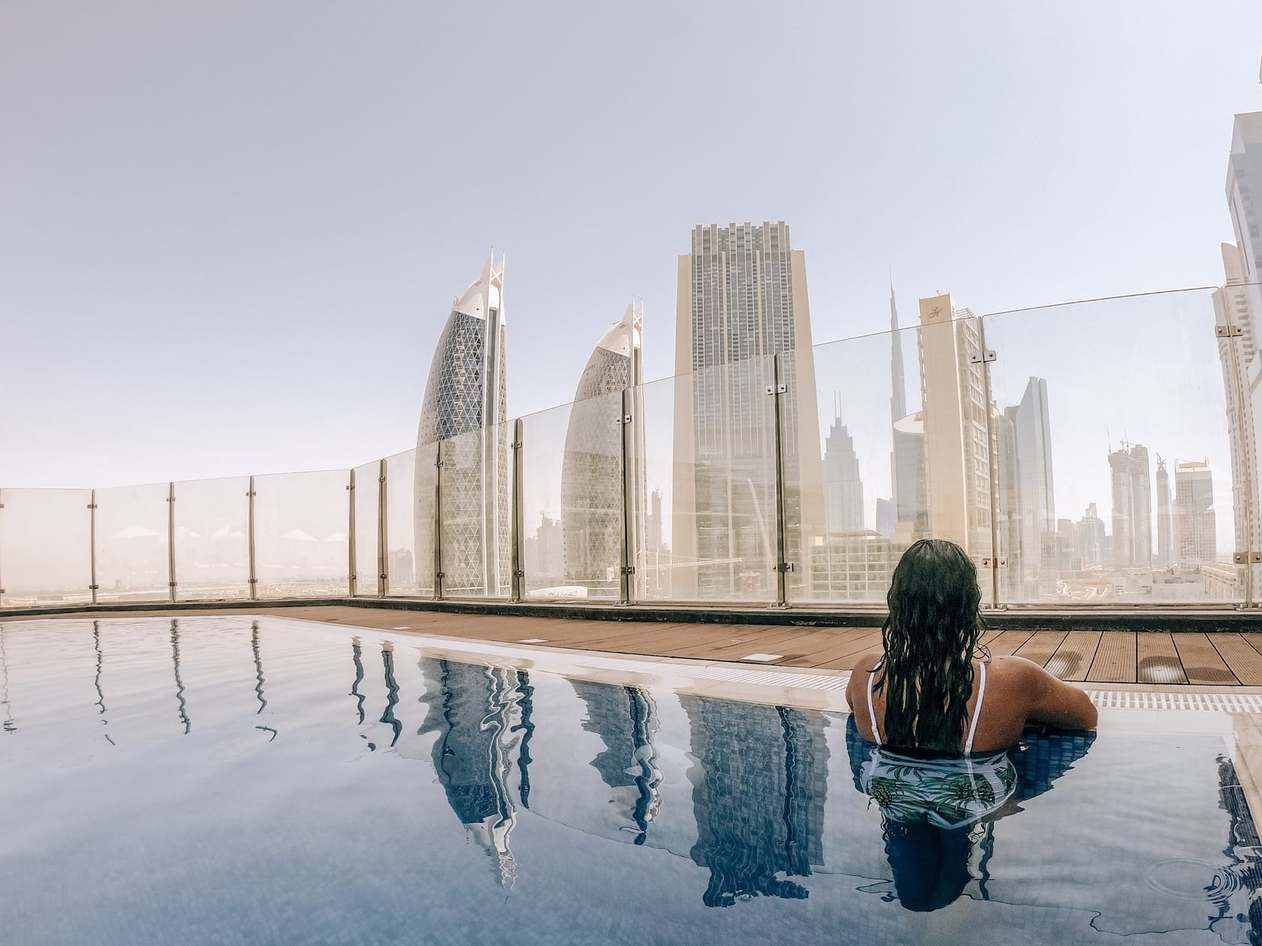 A woman in an infinity pool overlooking the Dubai skyline