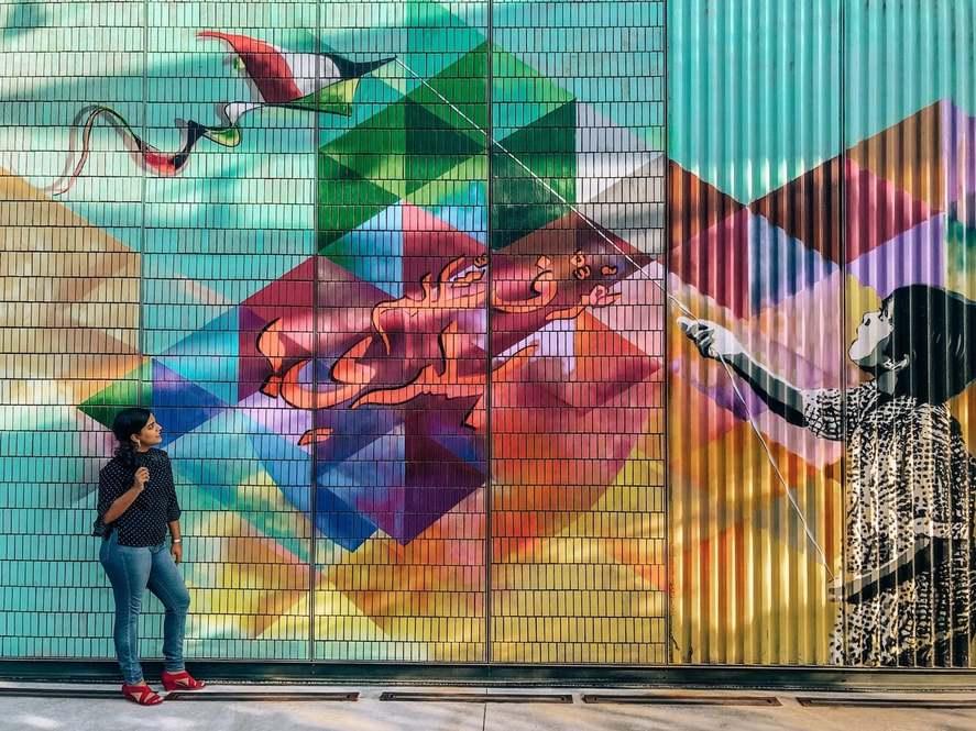 A woman admiring a mural in Dubai of a girl flying a kite