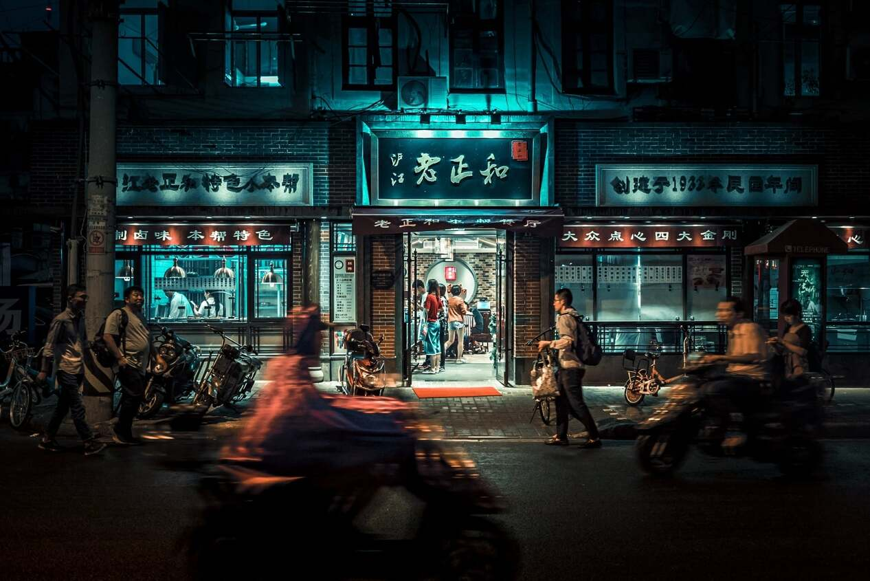 A shot of a Chinese store at night illuminated slightly with motorbikes buzzing past