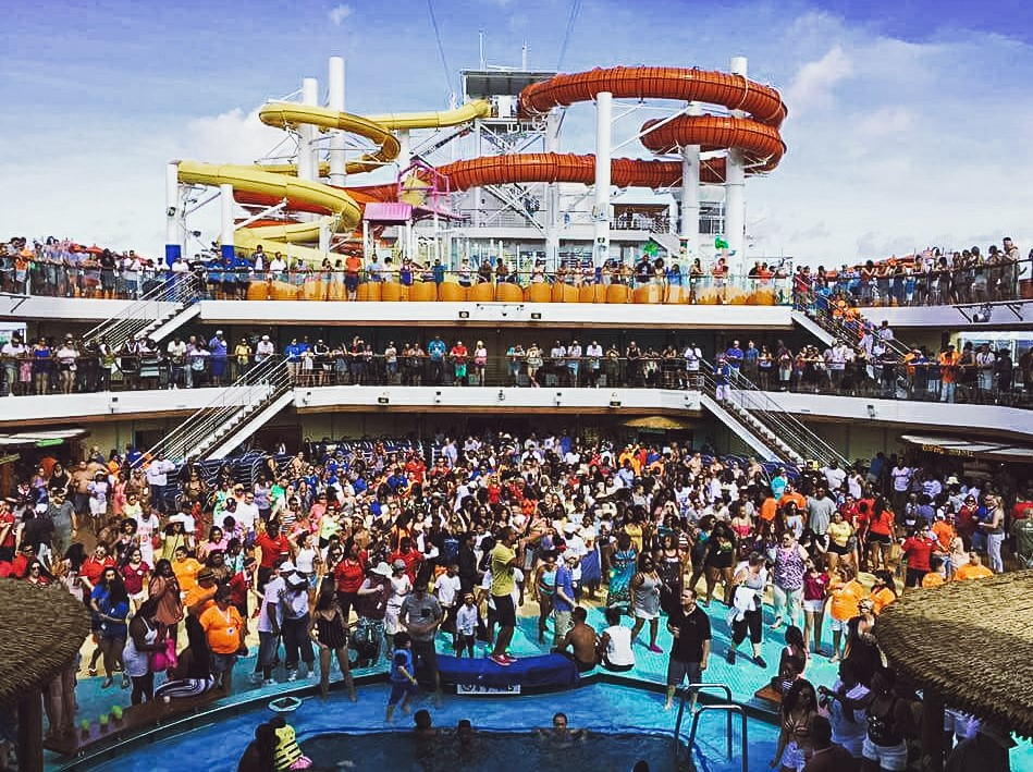 A super busy day on a cruise ship pool with thousands of people on deck together