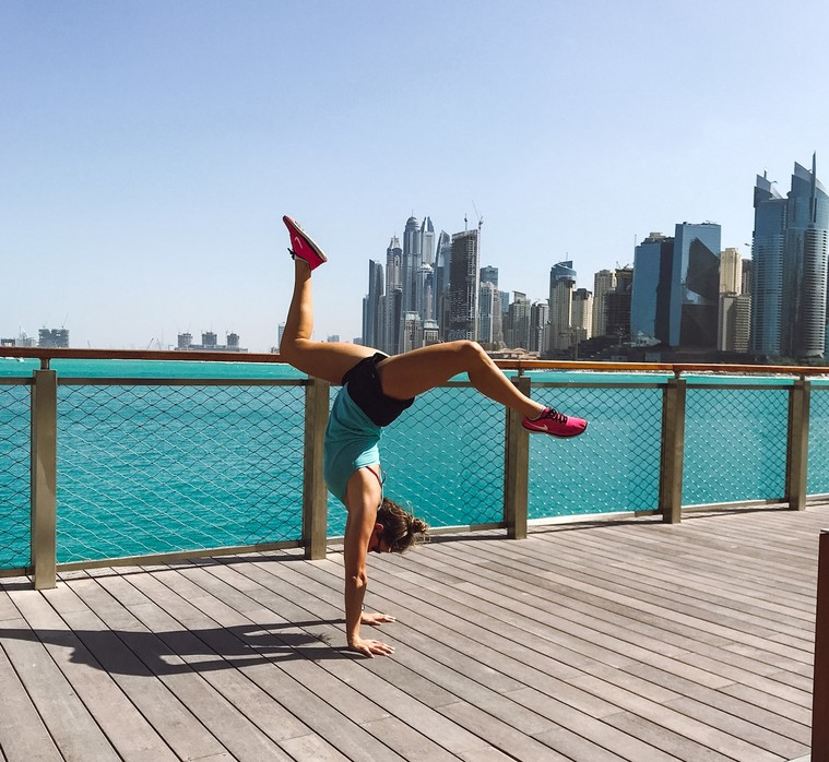A woman doing yoga in Dubai with water and skyline in background