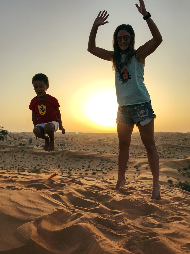 A woman and child jumping in the desert sand at sunset